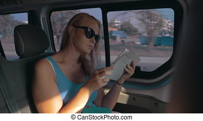 Girl with touch pad traveling by car