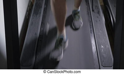 Adult male in sneakers walking on a treadmill and then...