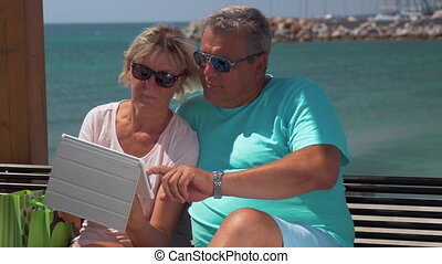 Senior couple using touch pad on waterfront