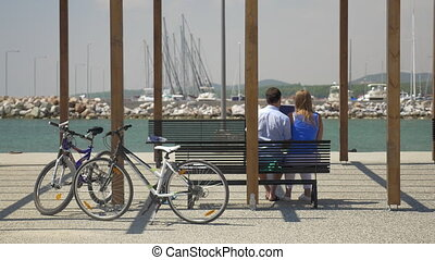 Couple with digital tablet on waterfront - Back view of...