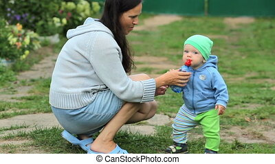 son holding a bottle of water and mother holding him in her arms. outdoor shot in the garden.
