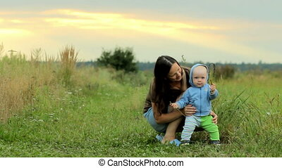 Happy family with baby playing in the field. Beautiful...