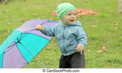 Kid, baby with umbrella in park. Summer scene in nature. Fun holidays. Childhood