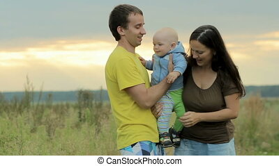Happy family with baby playing in the field Beautiful orange...