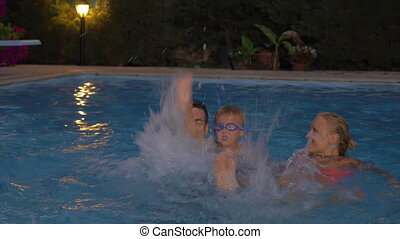 Happy family splashing water in the pool - Family with child...