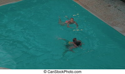 Parents and child swimming in the pool