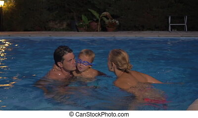 Parents and son bathing in the pool - Young parents and...