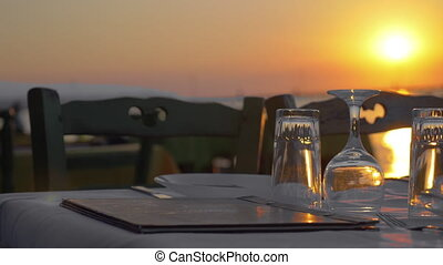 Served table in outdoor restaurant at sunset - Empty table...