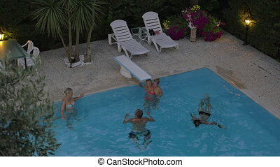 Family spending time in the outdoor pool - Family bathing in...