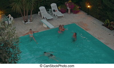Family relaxing in the swimming pool - High angle shot of...