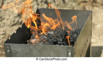 Flames with sparks on the coals in the grill outdoors....