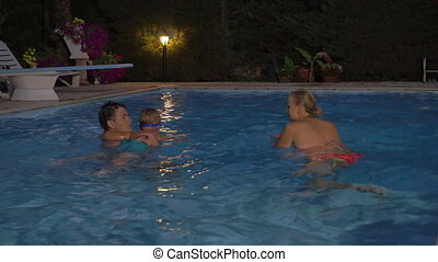 Parents teaching son to swim - Young parents and little son...