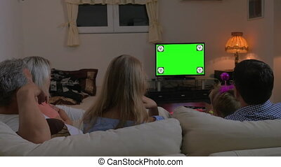 Family watching TV at home, chroma key - Back view of a...