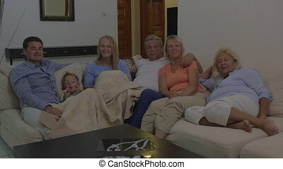 Big family watching TV in the evening