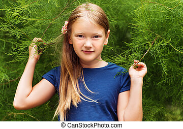 Outdoor portrait of a cute little girl of 8-9 years old...