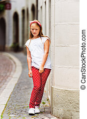 Outdoor fashion portrait of a ute little girl of 8-9 years...