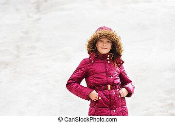 Winter portrait of a cute little girl of 7 years old, wearing maroon jacket