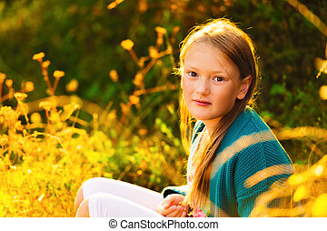 Outdoor portrait of a cute little girl of 8-9 years old at sunset
