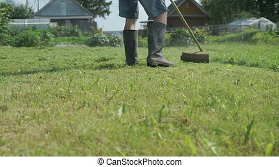 Worker cuts the grass with a lawnmower outdoors - The worker...
