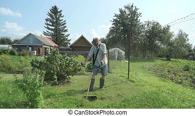 Worker mowing a grass using trimmer outdoors