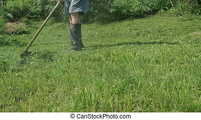 Man trimming grass in the garden using lawnmower outdoors
