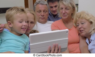 Big family with child watching tablet computer - Family with...