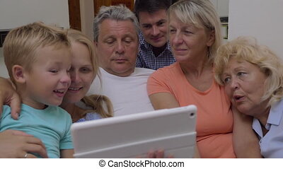 Family watching video on tablet computer - Big family with...