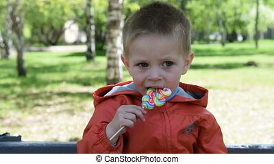 Kid with colorful candy outdoor - Little boy eating colorful...