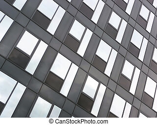 Glass facade - Modern black glass facade reflecting blue sky...