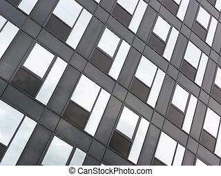Glass facade - Modern black glass facade reflecting blue sky...