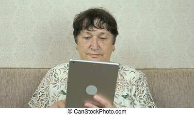 Elderly woman holding a silver digital tablet