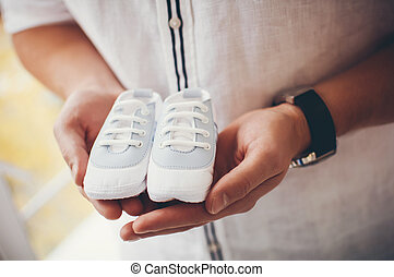 little white shoes for boys in beautiful male hands