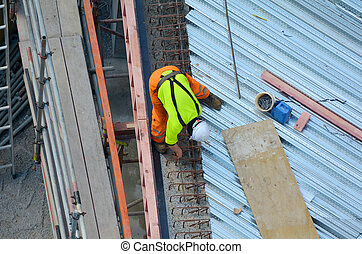 Construction worker making reinforcement in building site -...