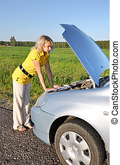 Young woman in her car breaks down. Engine failure