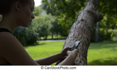 Teenager girl browsing web on mobile in the park - Teenager...