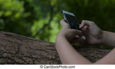 Girl using smart phone in the park - Close-up shot of a...