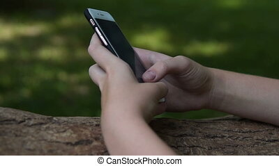 Girl typing on mobile phone in the park - Close-up shot of a...