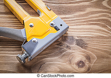 Staple gun on wooden board directly above construction...