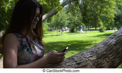 Girl browsing web on mobile outdoor - Teenager girl using...