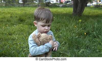 Child with toy bear friend in the park - Little boy hugging...