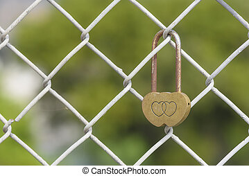 Closeup rusty heart shaped padlock locked on iron chain