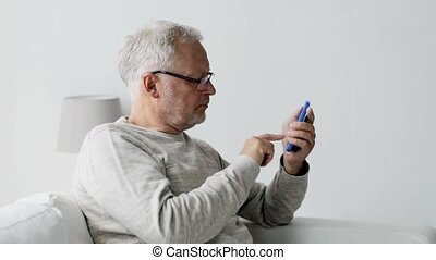happy senior man calling on smartphone at home