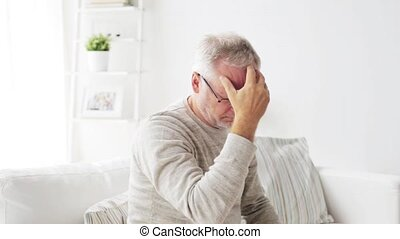 senior man suffering from headache at home 30 - health care,...