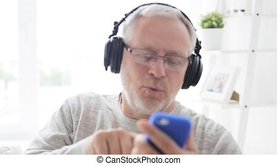 happy senior man with smartphone and headphones 17 -...