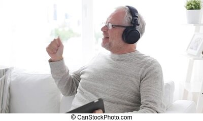 senior man with tablet pc and headphones at home -...