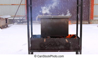 Metal smoker box standing on fire with red flame and smoke...