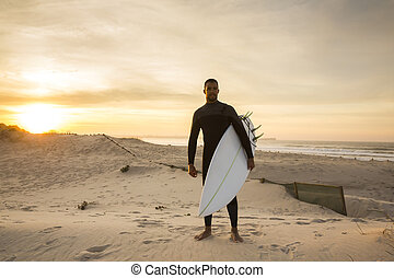 A surfer with his surfboard at the beach
