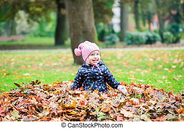laughing girl playing in the autumn park
