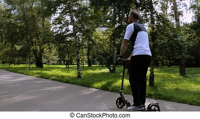 A man riding a scooter in a park, for a healthy lifestyle.