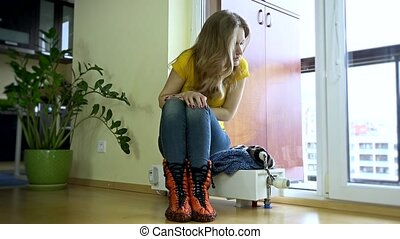 Young woman put,cap on sitting on cold radiator. Waiting for...